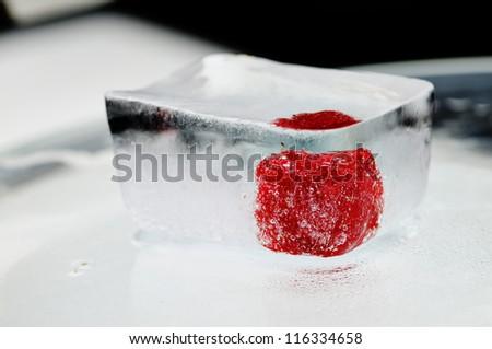 Fresh raspberry frozen in the ice cube.