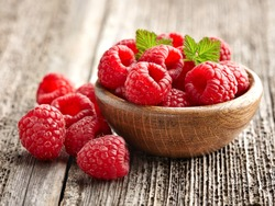 Fresh raspberry in a wooden plate