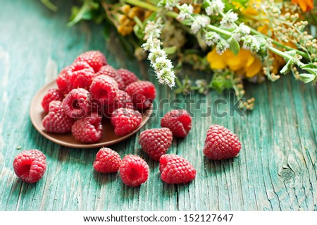 Fresh raspberry in ceramic plate on the blue wooden rustic desk with green summer herbs - stock photo