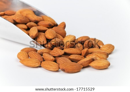 Fresh Raw Almonds in Aluminum Scoop Isolated on White Background.  Nuts are spilling out on solid bg with plenty of room for ad copy.