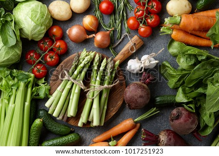 Fresh raw asparagus and other spring vegetables cooking in the kitchen, top view #1017251923