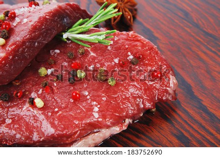 fresh raw beef fillet mignon on old retro style wood as background with rosemary peppercorn and salt