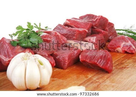 fresh raw beef meat slices over a wooden board with dill , green  and red hot peppers isolated over white background