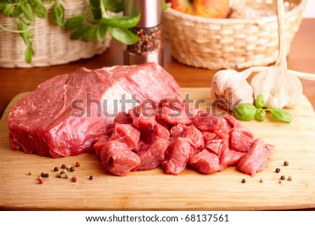 Fresh raw beef on wooden cutting board with garlic, pepper and basil