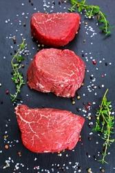 Fresh Raw Beef steak Mignon, with salt, peppercorns, thyme, garlic Ready to cook