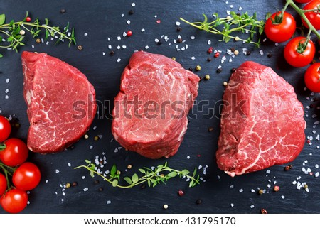 Fresh Raw Beef steak Mignon, with salt, peppercorns, thyme, tomatoes.