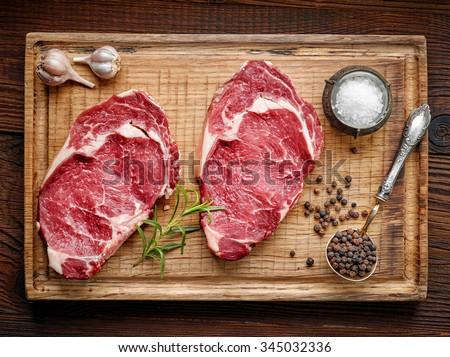 fresh raw beef steak on wooden cutting board, top view