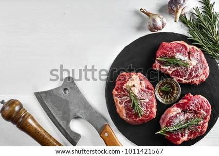 Fresh raw beef steaks with herbs, garlic, olive oil, pepper, salt and rosemary on black board: Tenderloin, Striploin, Rib Eye #1011421567