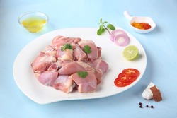 Fresh raw chicken pieces cut for curry with ingredients on pastel blue background