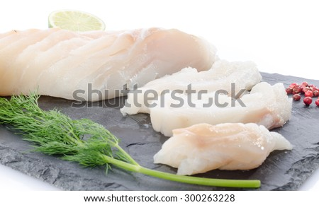 Fresh raw cod fillet on a slate plate, isolated on white