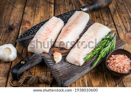 Fresh Raw cod loin fillet steaks on wooden board with butcher knife. wooden background. Top view ストックフォト ©