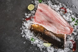 Fresh raw fillet fish and whole fish with spices on ice over dark stone background. Seafood, top view, flat lay