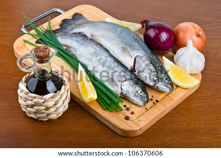 Fresh raw fish trout with oil, onions and lemon on a wooden background