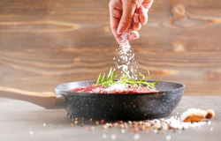 Fresh raw flank steak in the pan. The woman's hand adds salt to the meat. Ingredients are spices, rosemirine various sprouts and finally salt.