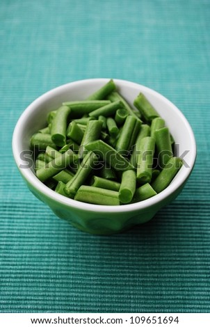 Fresh raw green beans in a ceramic bowl on green fabric gackground
