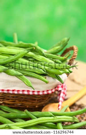 Fresh raw green beans in basket with green background (Selective Focus, Focus on the beans in the middle of the image)