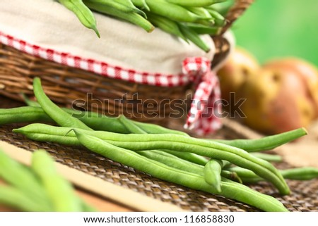 Fresh raw green beans in front of a basket with potatoes in the back (Selective Focus, Focus on the long bean one third into the image )