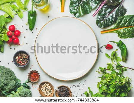 Fresh raw greens, unprocessed vegetables and grains over light grey marble kitchen countertop, wtite plate in center, top view, copy space. Healthy, clean eating, vegan, detox, dieting food concept