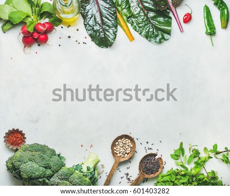 Fresh raw greens, unprocessed vegetables and grains over light grey marble kitchen countertop, top view, copy space. Clean eating, healthy, vegan, vegetarian, detox, dieting food concept