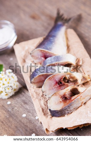 fresh raw herring on paper with salt and flower in studio #643954066