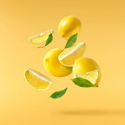 Fresh raw lemons with green leaves falling in the air isolated on yellow illuminating background. Food levitation or zero gravity conception. High resolution image