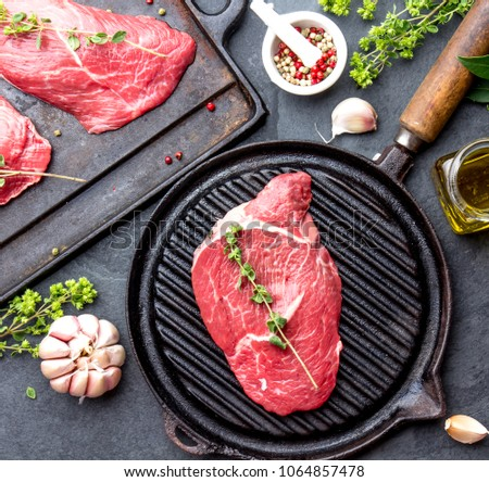 Fresh raw meat. Beef Tenderloin and marbled beef steaks on grill pan and frying board with seasoning, black background top view.