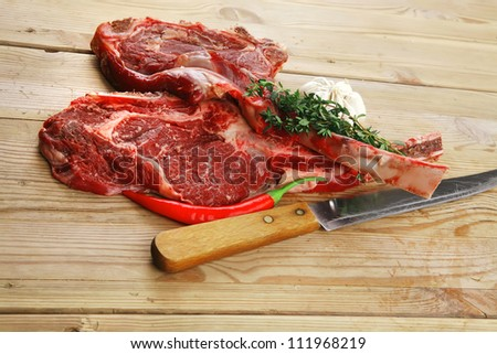 fresh raw meat : fresh red beef ribs with thyme , garlic and red chili pepper over wooden table