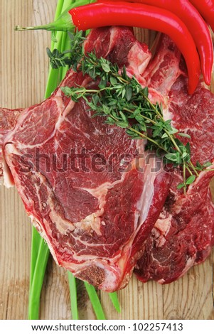 fresh raw meat : fresh red beef ribs with thyme , red chili pepper , and green onion on wooden board