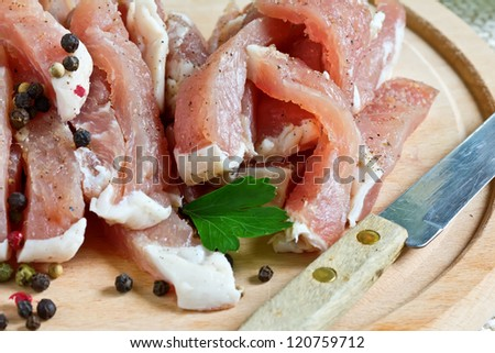 Fresh raw meat on wooden board on white table with whole pepper. Selective focus.