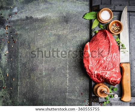 Fresh raw meat with herbs,spices and butcher knife on rustic background, top view, place for text. Cooking concept. Horizontal.