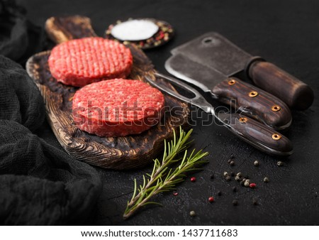Fresh raw minced homemade farmers grill beef burgers on vintage chopping board with spices and herbs and meat hatchet, fork and knife on black background.