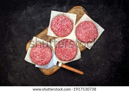 Fresh Raw Minced Homemade Grill Beef Steak Burgers. Raw BBQ Beef Burger Cutlets On Wooden Board, Overhead View. Raw Ground Beef Pork Meat Burger Cutlets For Grilling Or Frying. Raw Hamburger Patty.