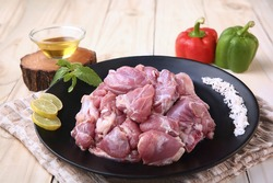 Fresh raw mutton pieces cut for curry with spices and ingredients on wooden table background