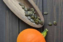 Fresh raw orange pumpkin with dry green pumpkin seeds on wooden plate over dark old wooden table background, top view.