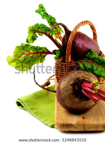 Fresh Raw Organic Beet Roots with Green Beet Tops in Wicker Basket on Napkin and Wooden Board closeup on White background