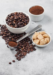 Fresh raw organic coffee beans in white bowl and powder on ligh table background with cane sugar and round steel scoop.