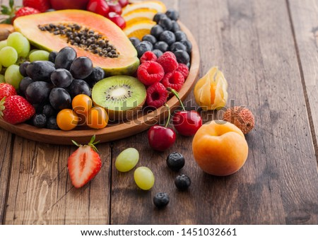 Fresh raw organic summer berries and exotic fruits in round wooden plate on wooden kitchen background. Papaya, grapes, nectarine, orange, raspberry, kiwi, strawberry, lychees, cherry Top view