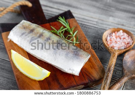 Photo of  Fresh raw pike perch fish fillet on cutting board