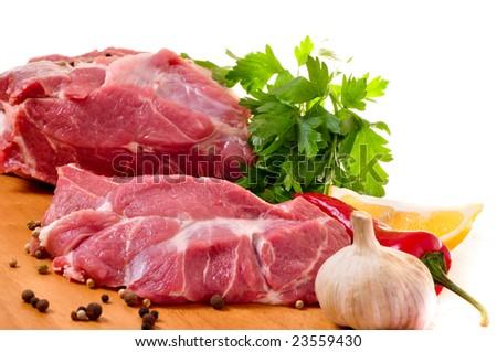 Fresh raw pork on board with fresh, vegetables. Garlic, pepper, parslay, lemon, spices.