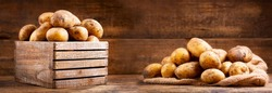 fresh raw potatoes in a wooden box on wooden background