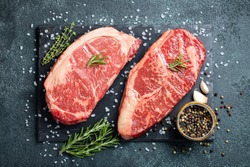 Fresh raw Prime Black Angus beef steaks on stone board: Striploin, Rib Eye. Top view. On a dark background