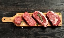 Fresh raw Prime Black Angus beef steaks on wooden board: Tenderloin, Denver Cut, Striploin, Rib Eye