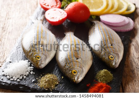 Fresh raw raw sarpa salpa fish with lemon, vegetables and spices closeup on a slate board on a table. Horizontal