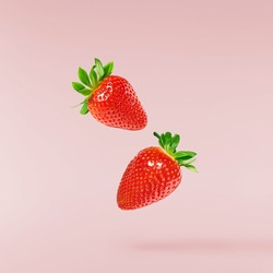 Fresh raw ripe strawberry with green leaves falling in the air isolated on pink background. Food levitation or zero gravity conception. Creative food layout, High resolution image