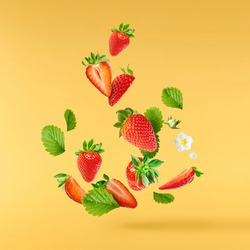 Fresh raw ripe strawberry with green leaves falling in the air isolated on yellow background. Food levitation or zero gravity conception. Creative food layout, High resolution image