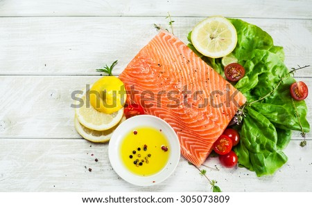Fresh raw salmon fillet on wooden rustic table with place for your text. Top view seafood photo. Healthy food, diet or cooking concept.