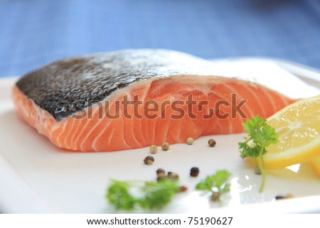 Fresh raw salmon on a white plate with pepper, parsley and lemon