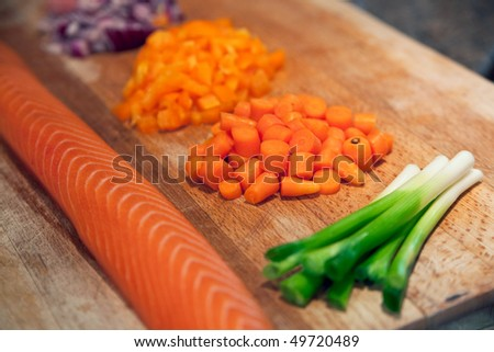 Fresh raw salmon on a wooden chopping board in a domestic kitchen, next to spring onions, chopped carrots, yellow pepper, and red onion.