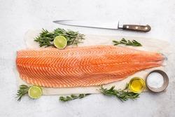Fresh raw salmon or trout sea fish fillet with spices and herbs on white background, top view