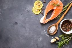Fresh raw salmon steak, lemon, herbs, spices, wooden spoon on dark rustic concrete background. Food frame. Ingredients set for making healthy dinner. Healthy/diet concept. Space for text. Fresh fish